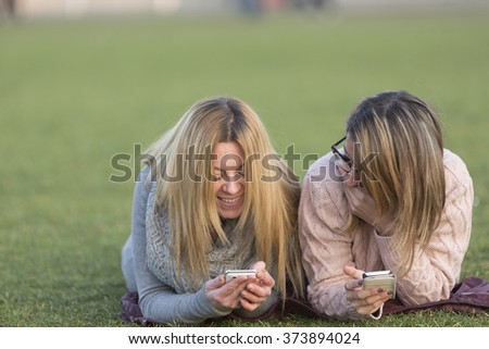 Funny girls looking excited to something in a mobile phone - stock photo