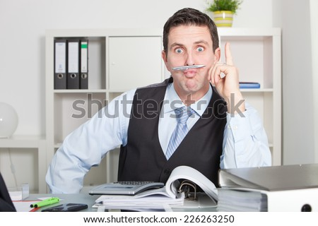 Funny Good Looking Young Office Man Holding Pen Between Lip and Nose at His Table Area, Looking at the Camera. - stock photo