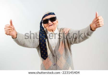 Funny grandma's studio portarit with a tie on her forehead, showing thumbs up - stock photo