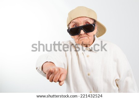 Funny grandma's studio portrait  wearing eyeglasses and baseball cap who kicks with  her fist , isolated on white - stock photo