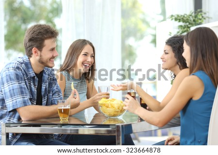 Funny group of 4 friends having a conversation and drinking at home - stock photo