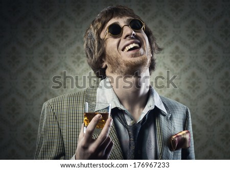 Funny guy holding a glass of whisky and posing against vintage wallpaper.