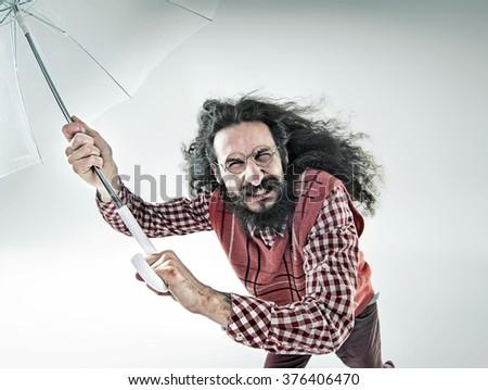 Funny guy holding an umbrella - stock photo