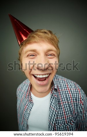 Funny guy laughing at camera on fool�s day - stock photo