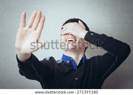 funny guy laughs, turns away and closes his eyes to avoid seeing - stock photo