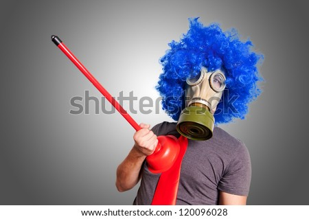 funny guy with gas mak, blue wig and red plunger on grey background - stock photo