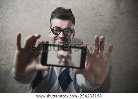 Funny guy with glasses taking a self picture with a smartphone - stock photo