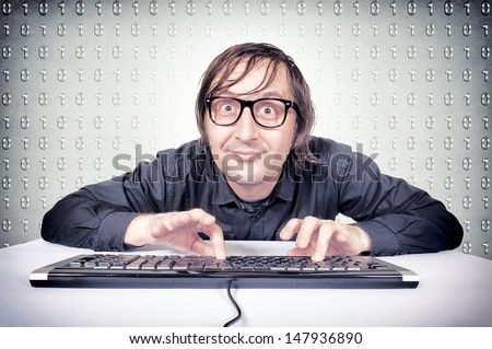 Funny hacker typing on the keyboard - stock photo