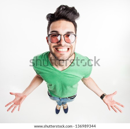 funny handsome man with hipster glasses showing his palms and smiling large  - wide angle shot - stock photo