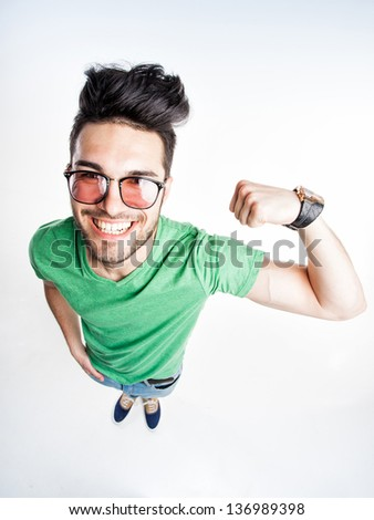 funny handsome man with hipster glasses showing muscles - wide angle shot - stock photo