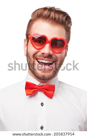 Funny handsome smiling man isolated on white background wearing heart shaped sunglasses. - stock photo