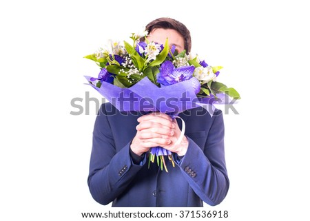 funny handsome young man with dark suit with a beautiful bouquet in the hands of white and purple flowers isolated on a white background - stock photo