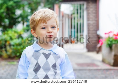 Funny happy and smiling blond kid boy on way to summer school, nursery or kindergarten. Son warm summer sunny day. In white fashion clothing. - stock photo