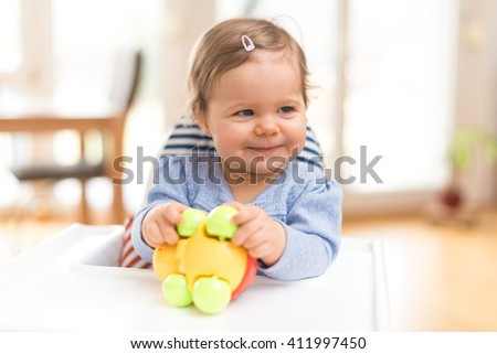 Funny Happy Baby Is Laughing And Playing With A Toy - stock photo