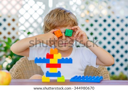 Funny happy blond child playing with lots of colorful plastic blocks indoor. Active kid boy having fun with building and creating. - stock photo