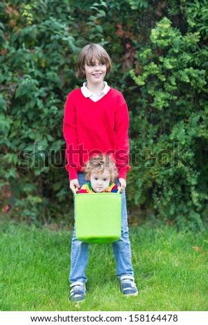 Funny happy brother and baby sister playing with a laundry basket - stock photo