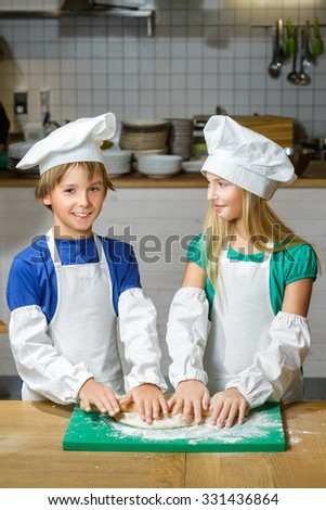 Funny happy chef boy width girl cooking at restaurant kitchen and rolls the dough with a rolling pin - stock photo
