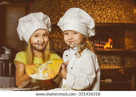 Funny happy chef girl cooking at restaurant kitchen and show pizza - stock photo