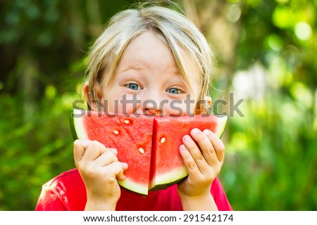 Funny happy child eating watermelon outdoors, making a smile - stock photo