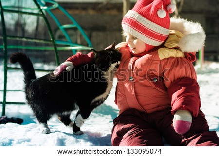 Funny happy child playing with cat outdoors in winter.