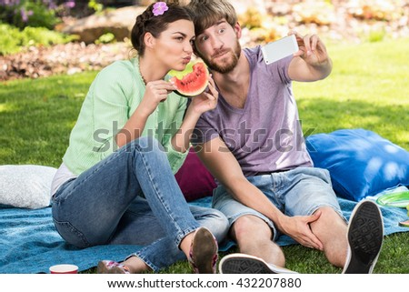 Funny happy couple taking a self photo on picnic party