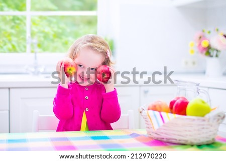 Funny happy laughing child, adorable toddler girl with curly hair wearing a pink shirt, eating red and green apples for healthy snack sitting in a white sunny kitchen with window at home