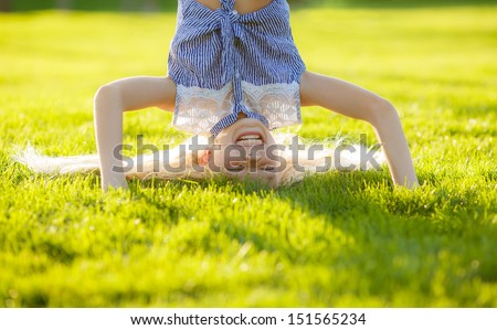 Funny happy little girl standing on her head on the grass in the park.  - stock photo