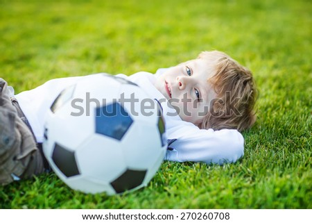 Funny happy little kid boy of 4 resting after playing soccer with football on football field, outdoors. Active leisure and lifestyle with little children - stock photo
