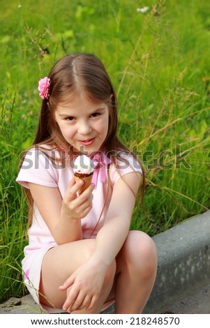 Funny happy toddler girl wearing white summer dress sitting on a green lawn eating vanilla and chocolate ice cream cone in a sunny garden or park