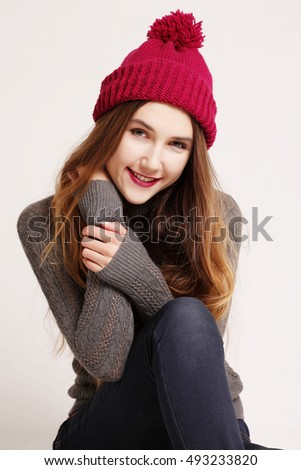 Funny hipster girl in knitted grey sweater and beanie marsala hat. Bright lips, having fun. Trendy casual fashion outfit in winter.