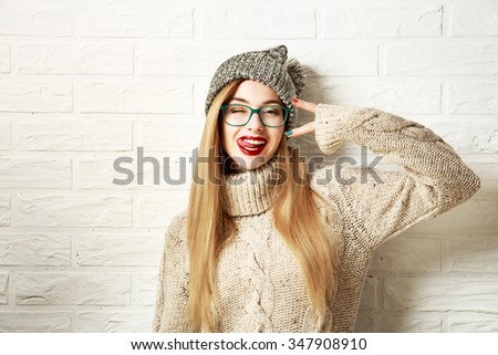 Funny Hipster Girl in Knitted Sweater and Beanie Hat Going Crazy at White Brick Wall Background. Trendy Casual Fashion Outfit in Winter. Toned Photo with Copy Space. - stock photo