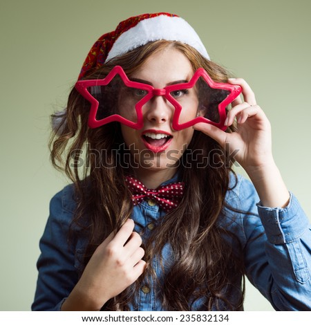 Funny hipster girl in super size star shape glasses wearing xmas santa hat over olive copy space background - stock photo