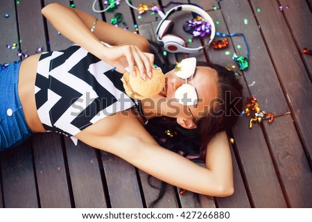Funny Hipster Girl laying on wooden floor,hipster outfit Going Crazy at tropical island,Trendy Casual Fashion Outfit in summer,spring.Toned Photo,Copy Space.music on cool big headphones,burger,summer - stock photo