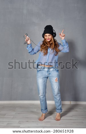 Funny hipster girl listening to music on headphones and dancing barefoot. The concept of modern youth culture. - stock photo