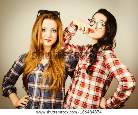 Funny hipster girls wearing plaid shirt and retro glasses making faces pretending to wear a mustache. Retro filter effect added. - stock photo