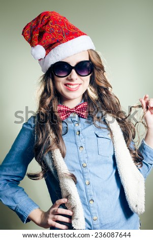 Funny hipster pretty girl in sunglasses wearing xmas santa hat over olive copy space background - stock photo