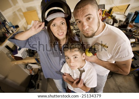 Funny Hispanic family in garage with variety of tools - stock photo