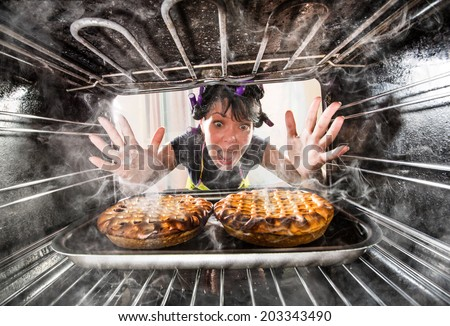 Funny Housewife overlooked cakes in the oven, so she had scorched, view from the inside of the oven. Housewife perplexed and angry. Loser is destiny! - stock photo
