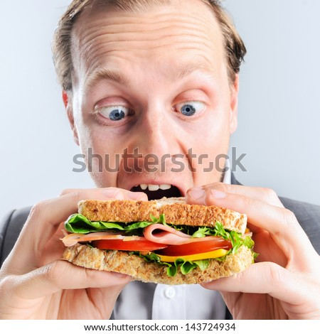 Funny humorous man eating a sandwich with exaggerated wide eye comical expression - stock photo