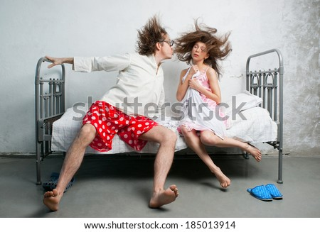 Funny husband and wife sitting on the bed - stock photo