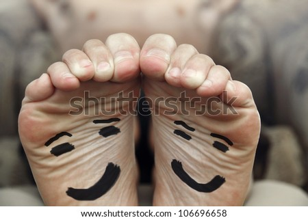 Funny image of a pair of bare male feet with happy smiley face drawn on bottom - stock photo