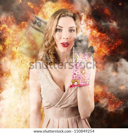Funny image of a surprised woman cook setting the kitchen alight in a burst of fire and smoke.  Bad cooking - stock photo