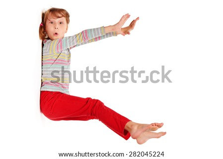 Funny image of amazed emotional little girl sticked to white wall with stretched hands and legs, isolated on white  - stock photo