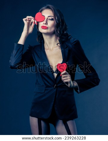 Funny Joyful Girl with Valentine Hearts over her Eyes. Laughing Young Woman in love. on black background. vintage toning - stock photo