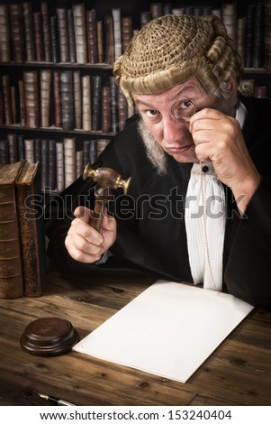 Funny judge looking through an antique monocle - stock photo