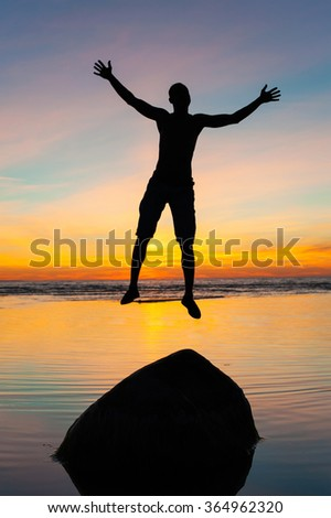 Funny jumping on the beach for joy. Jumping on the stone man silhouette on spectacular sunset background. Multicolored vibrant vertical outdoors image. - stock photo