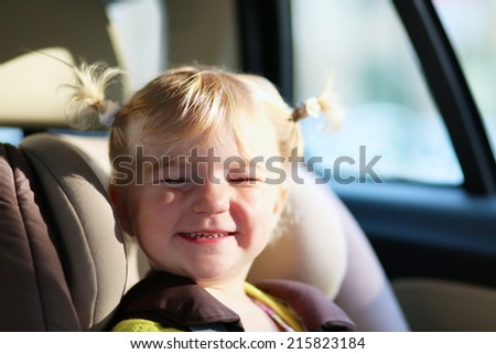 Funny kid, adorable happy toddler girl sitting in the modern red car in a child seat locked with safety belt enjoying family vacation trip on summer weekend - stock photo