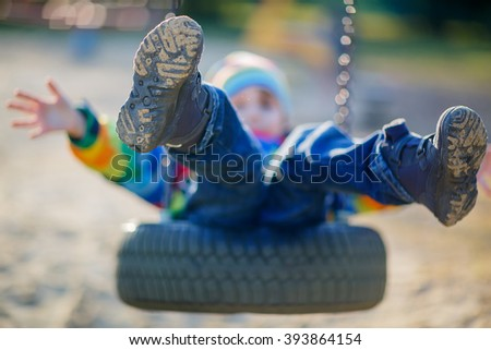 Funny kid boy having fun with chain swing on outdoor playground. child swinging on warm sunny spring or autumn day. Active leisure with kids. Selective focus - stock photo