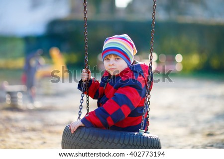 Funny kid boy having fun with chain swing on outdoor playground. child swinging on warm sunny spring or autumn day. Active leisure with kids. Boy wearing colorful clothes - stock photo