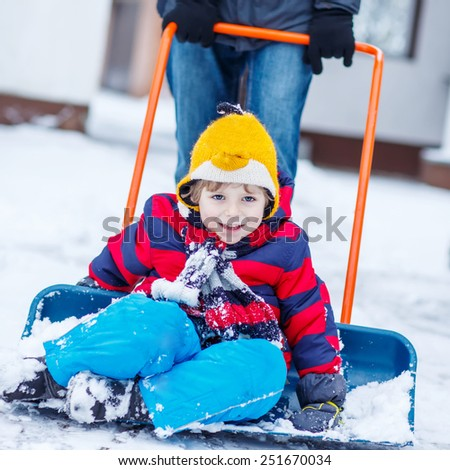 Funny kid boy having fun with riding on snow shovel during his father cleaning road from snow, outdoors  on cold day. Active outoors leisure with children in winter.